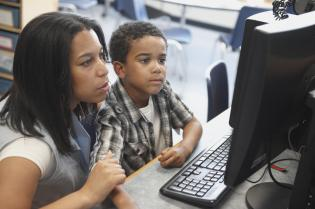 Teacher And Male Student Looking At Computer