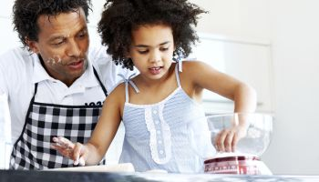 Father and daughter together baking