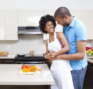 Man embracing woman preparing vegetables