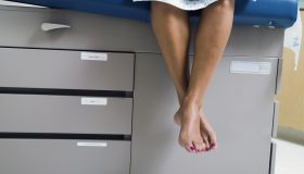 View of a patient's legs dangling from a bed