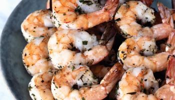 Grilled shrimp skewered with rosemary twigs on stoneware platter