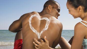 Hispanic woman drawing heart in sunscreen on boyfriend's back