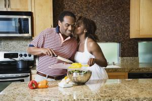 African couple fixing healthy meal in modern kitchen