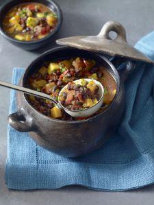 Brazilian black bean and pumpkin soup served in rustic casserole dish, close-up