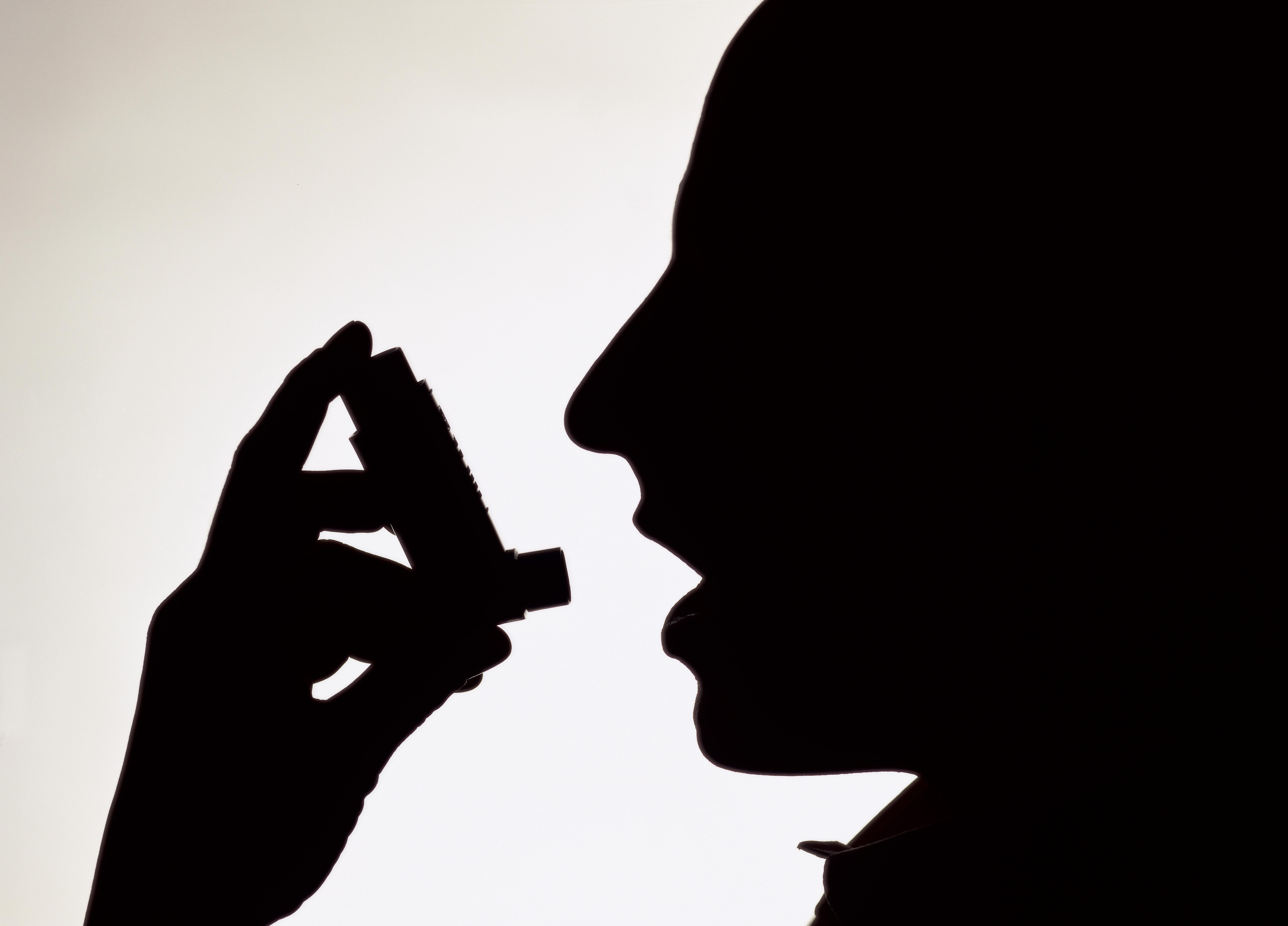 Side profile silhouette of a person using an inhaler