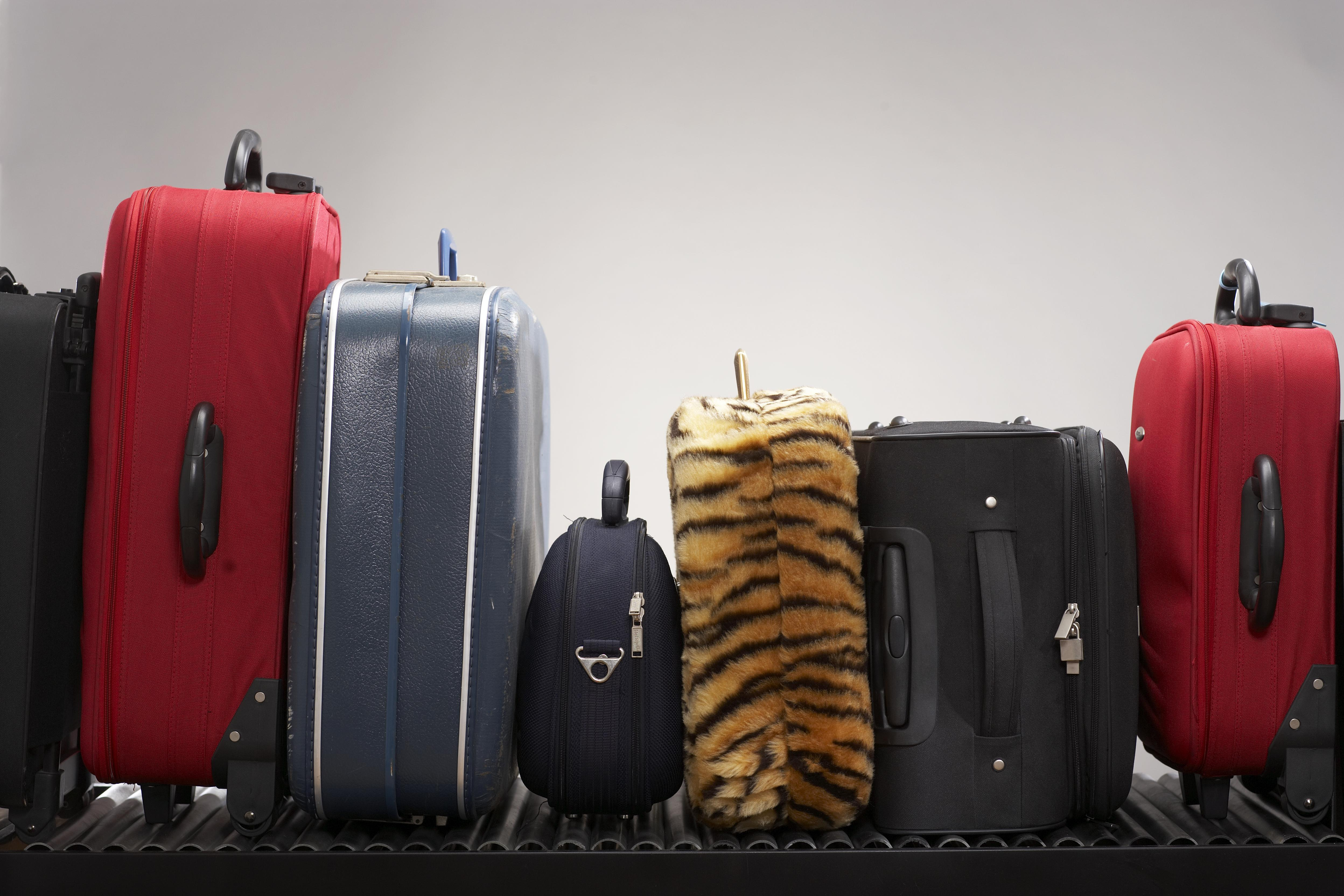 Various suitcases on conveyor belt