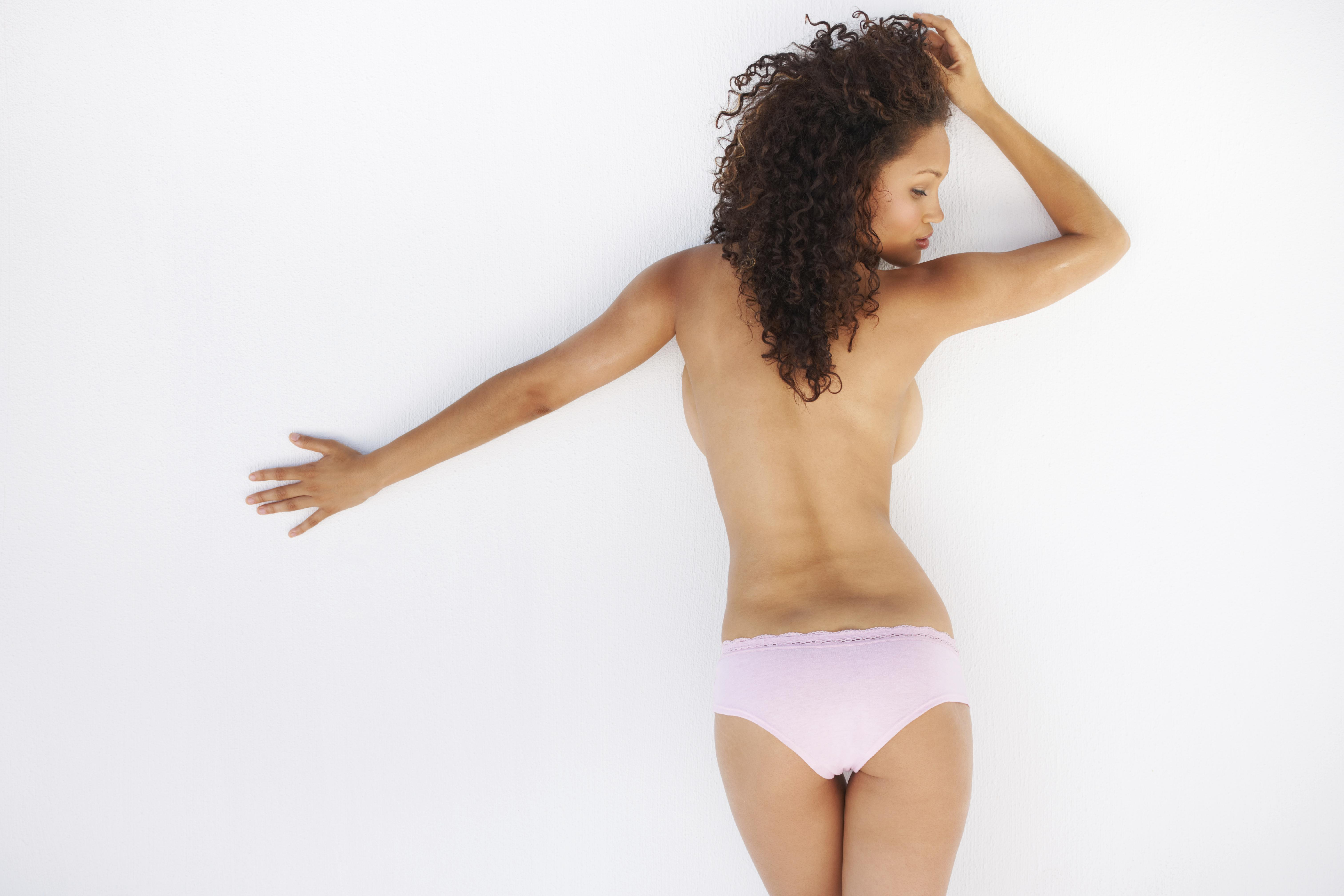Rear view of a topless young woman leaning against a wall with her arm spread out
