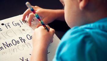 Preschool girl copying her letters