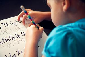 Preschool girl copying her letters
