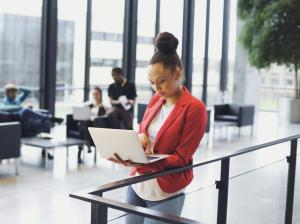 Young afro american woman standing by a railing using laptop with people working in background . Young businesswoman in modern office enviornment.