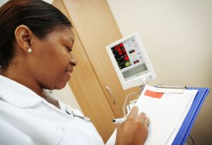 Nurse in white uniform writing updates to her patients records