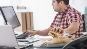 Mixed race businessman eating and working at desk