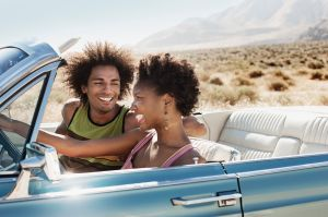 A young couple, man and woman in a pale blue convertible on the open road