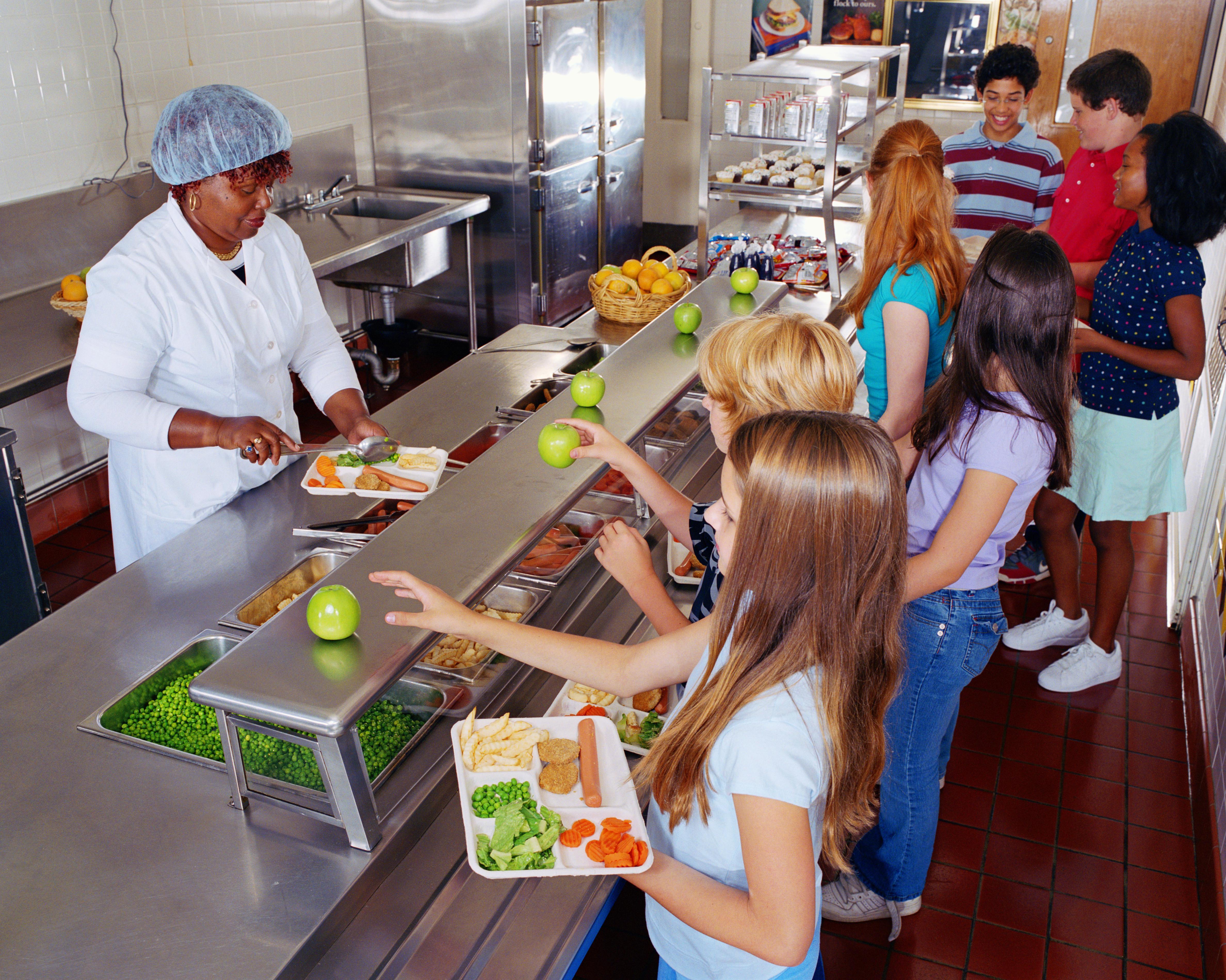 Woman serving food to schoolchildren (10-13) in cafeteria