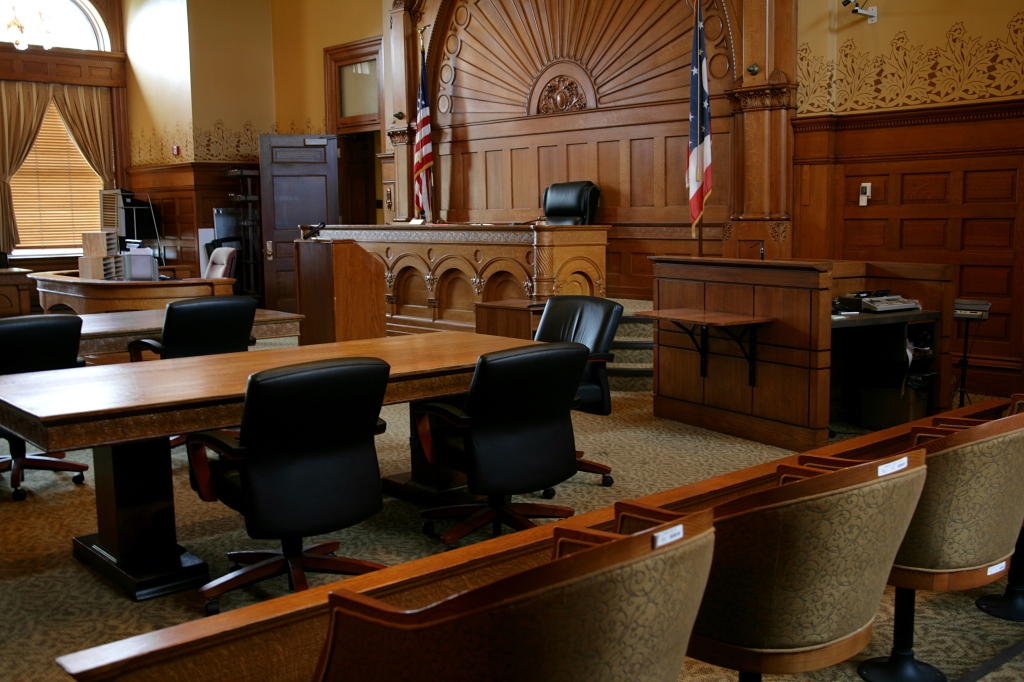 An empty, brown-paneled courtroom with flags