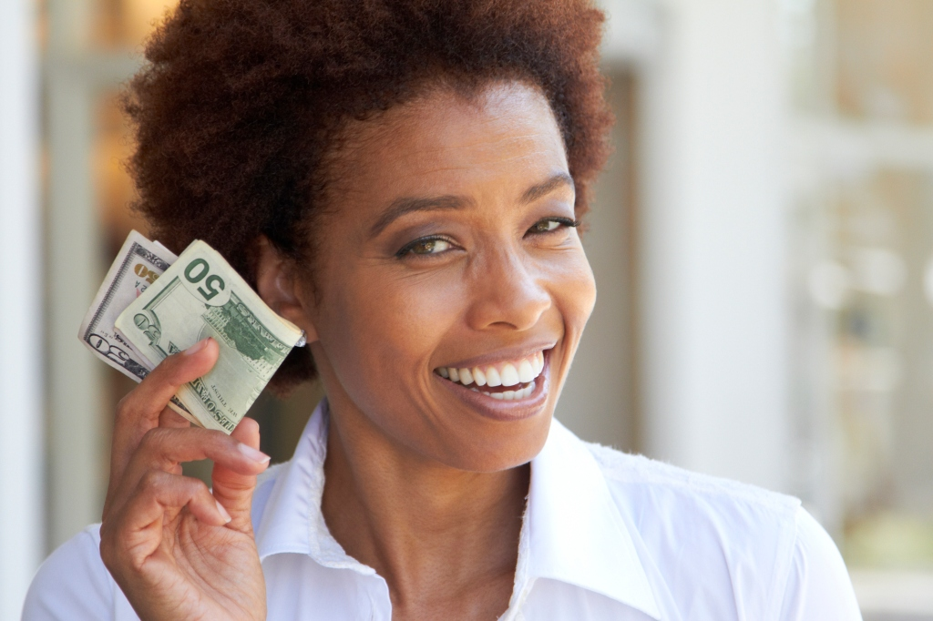African American woman holding 50 dollar bill