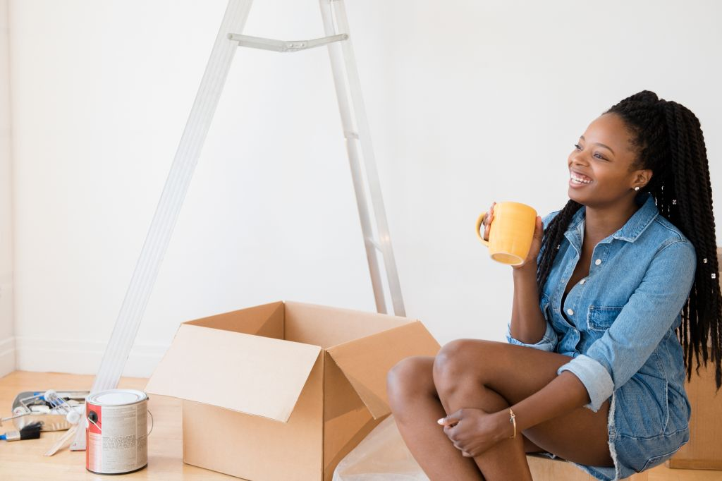 Black woman drinking coffee in new home