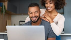 Black couple paying bills online at home