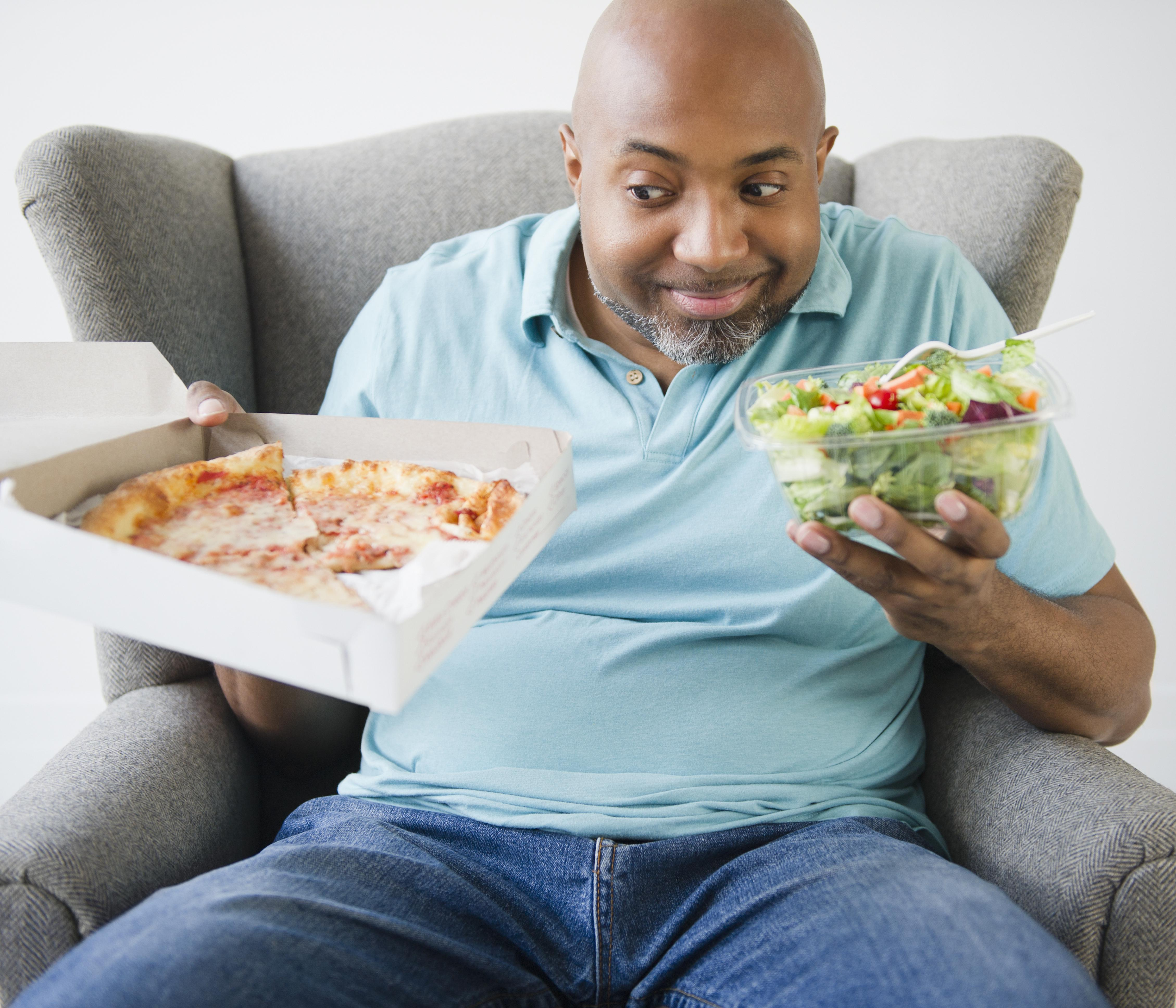 African American deciding between salad and pizza