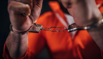 Man prisoner in orange jumpsuit wearing handcuffs