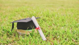 Mortarboard And Diploma On Field