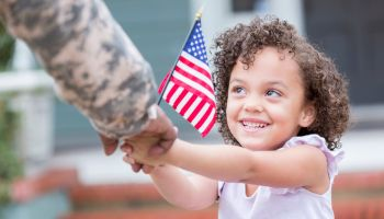 Adorable little girl holds her military dad's hand