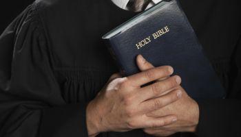 Hispanic pastor holding Bible